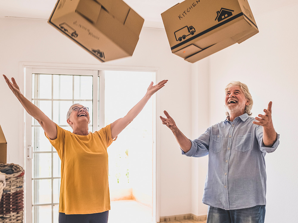 A man and woman throwing boxes up in the air.
